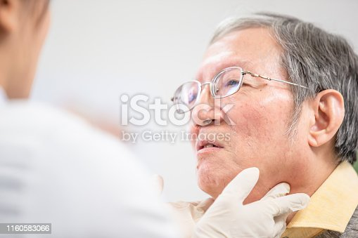 1049772134istockphoto Female doctor check throat 1160583066