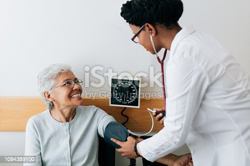 A female doctor checking blood pressure to a senior patient and smiling.