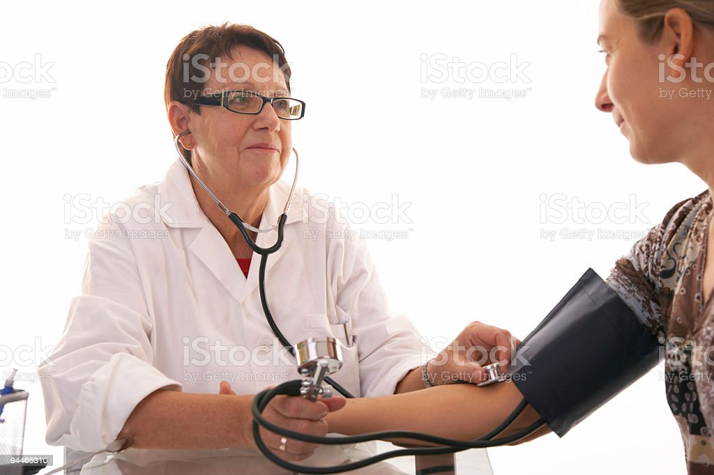 female doctor checking blood pressure with smile royalty-free stock photo