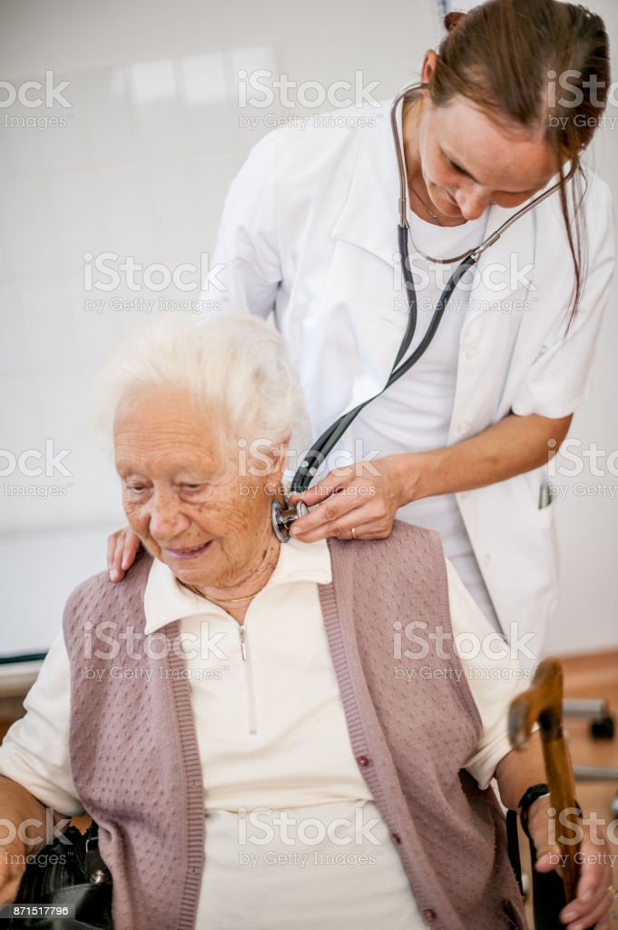 Female Doctor Checking Glands Of Senior Woman  In Rest Home stock photo