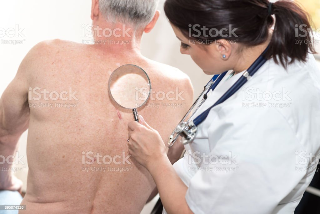 Female doctor checking skin of senior patient stock photo