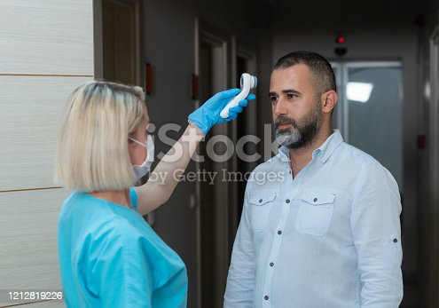 Female doctor checking temperature at patient with infrared tool in hospital