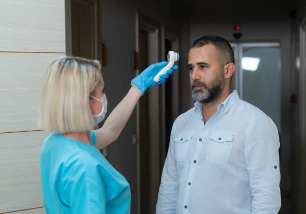 Female doctor checking temperature at patient with infrared tool in hospital stock photo