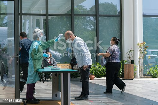 istock Female doctor checking temperature at patient with infrared tool in hospital 1221611535