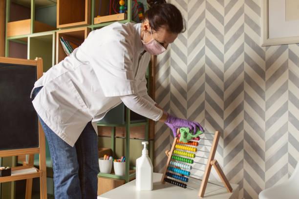 Female doctor cleaning kindergarten stock photo
