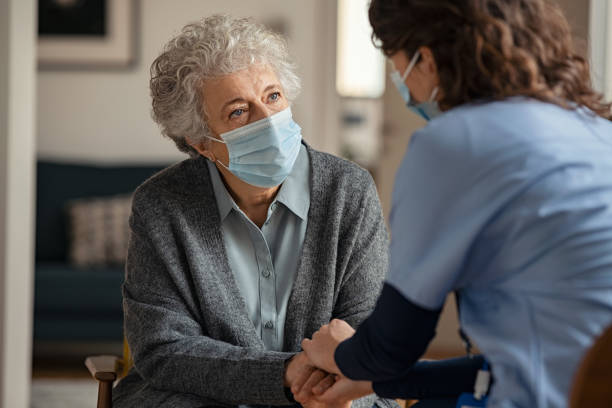 Female doctor consoling senior woman wearing face mask during home visit stock photo