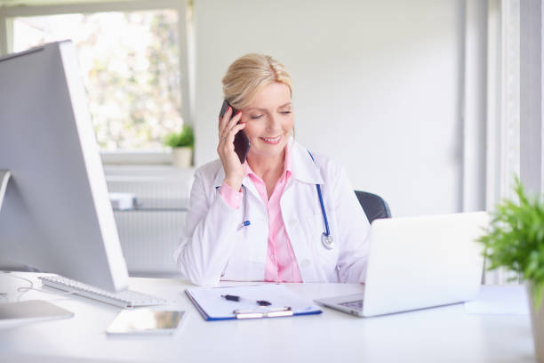 female doctor consulting with her patient on mobile phone - nurse on phone stock photos and pictures