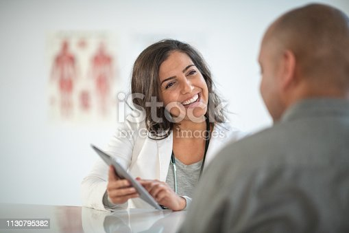 A female doctor smiles while consulting her male patient. The doctor is holding a digital tablet and is reviewing the patient's medical information.