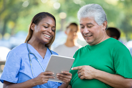 Female doctor discusses patient's healthcare with  senior man at outdoor health fair