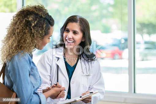 istock Female doctor discusses something with young mixed race patient 958886668