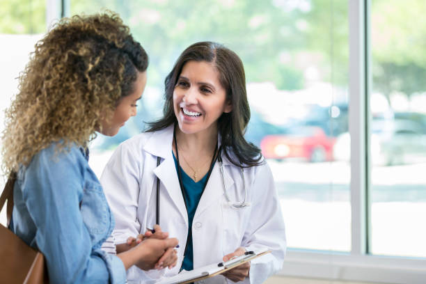 female doctor discusses something with young mixed race patient - exam stock pictures, royalty-free photos & images