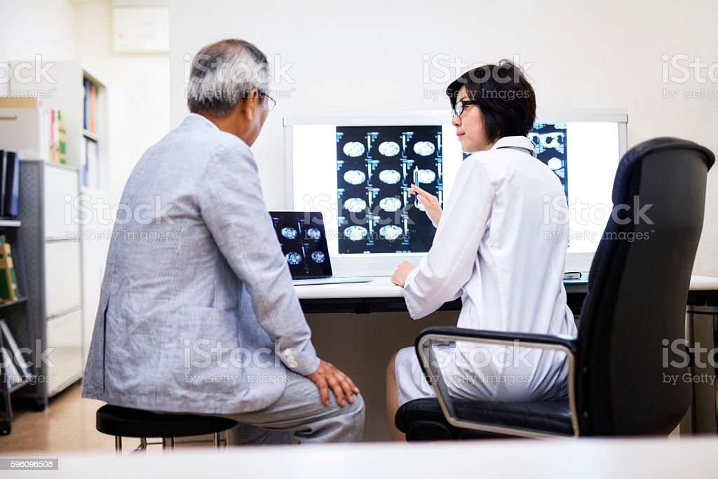 Female doctor discussing with man over MRIs in hospital royalty-free stock photo