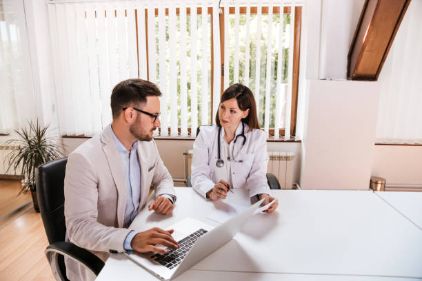 Female doctor discussing with manager. stock photo