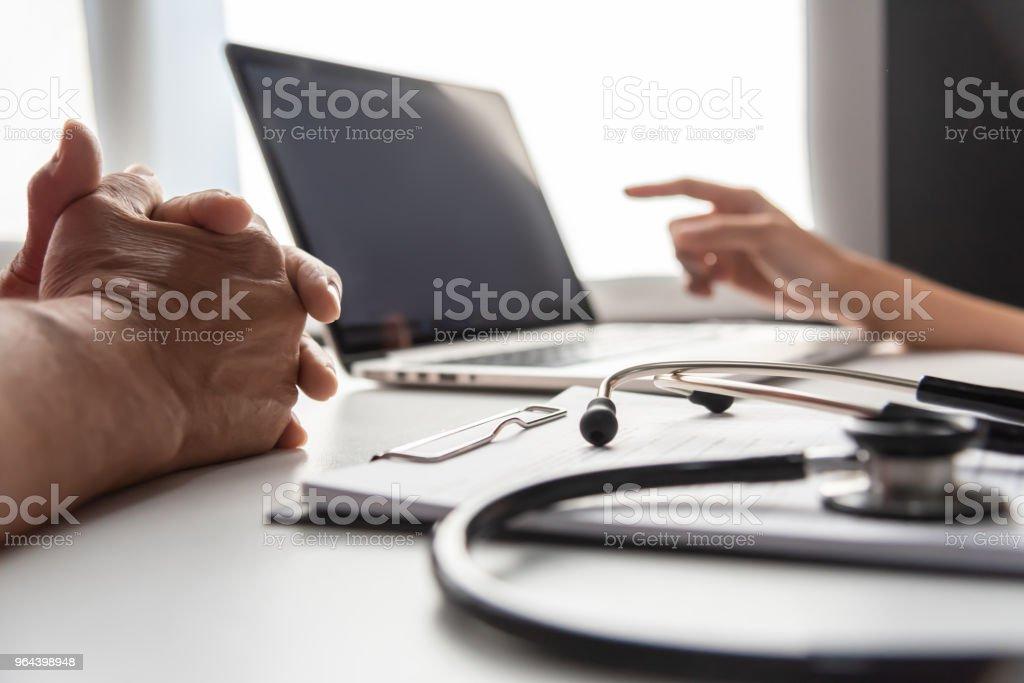 Vrouwelijke arts met senior man patiënt bespreken. - Royalty-free Alleen mannen Stockfoto