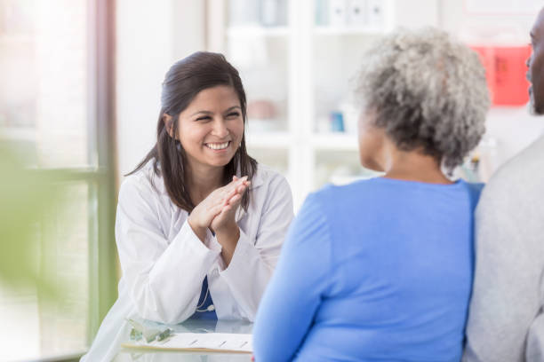 Female doctor enjoys giving patients good news stock photo