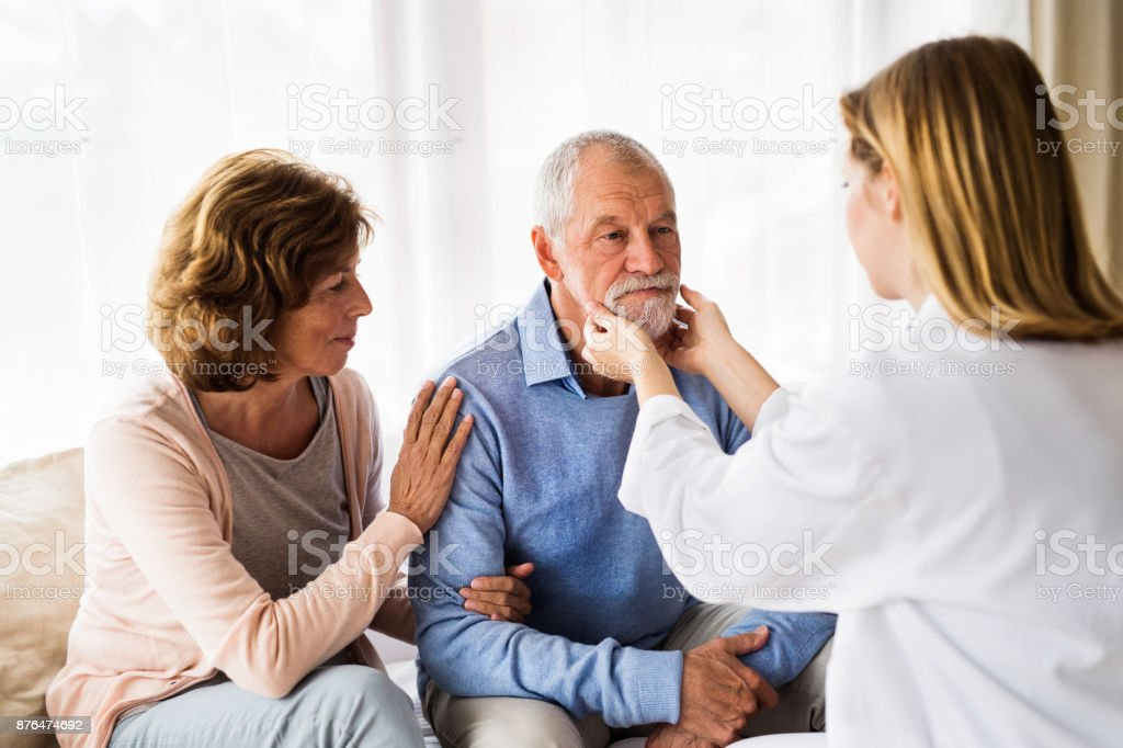 Female doctor examining a senior man. stock photo