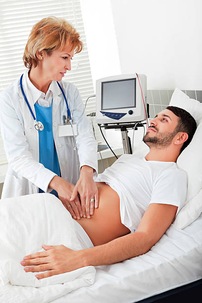 female doctor examining a young man - human abdomen stock pictures, royalty-free photos & images