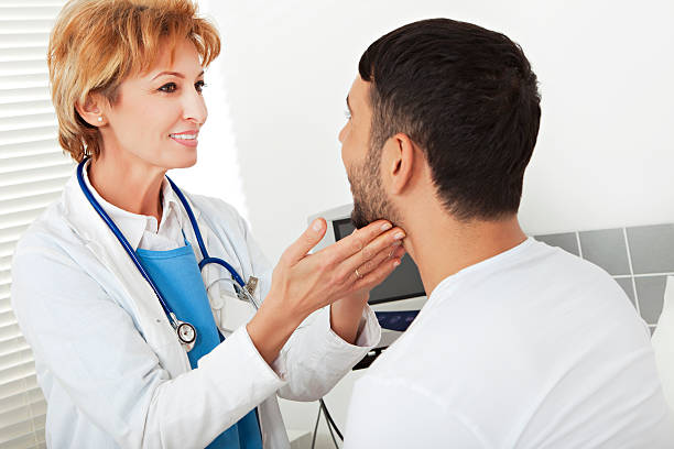 Female doctor examining a young man Close-up of a female doctor doing a medical examinationCheck out other medical images from my portfolio: endocrine system stock pictures, royalty-free photos & images