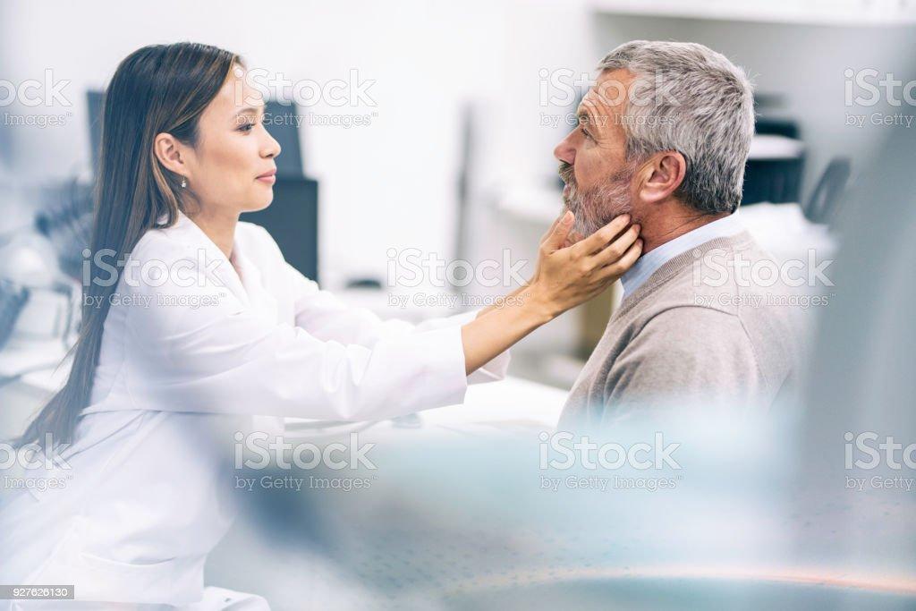 Ärztin untersucht ein älterer Patient Kehle – Foto