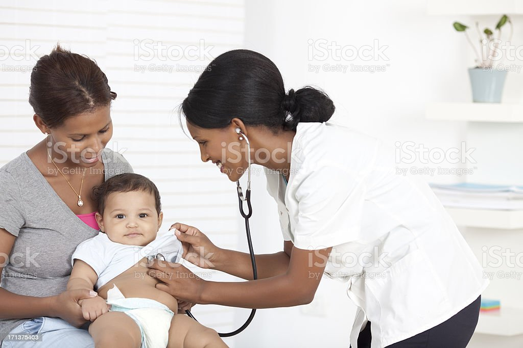 Female doctor examining baby boy. stock photo