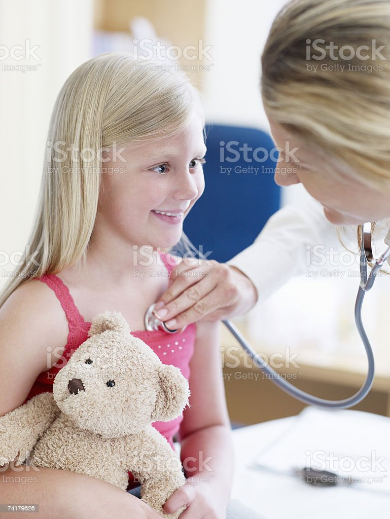 Female doctor examining girl with teddy bear royalty-free stock photo