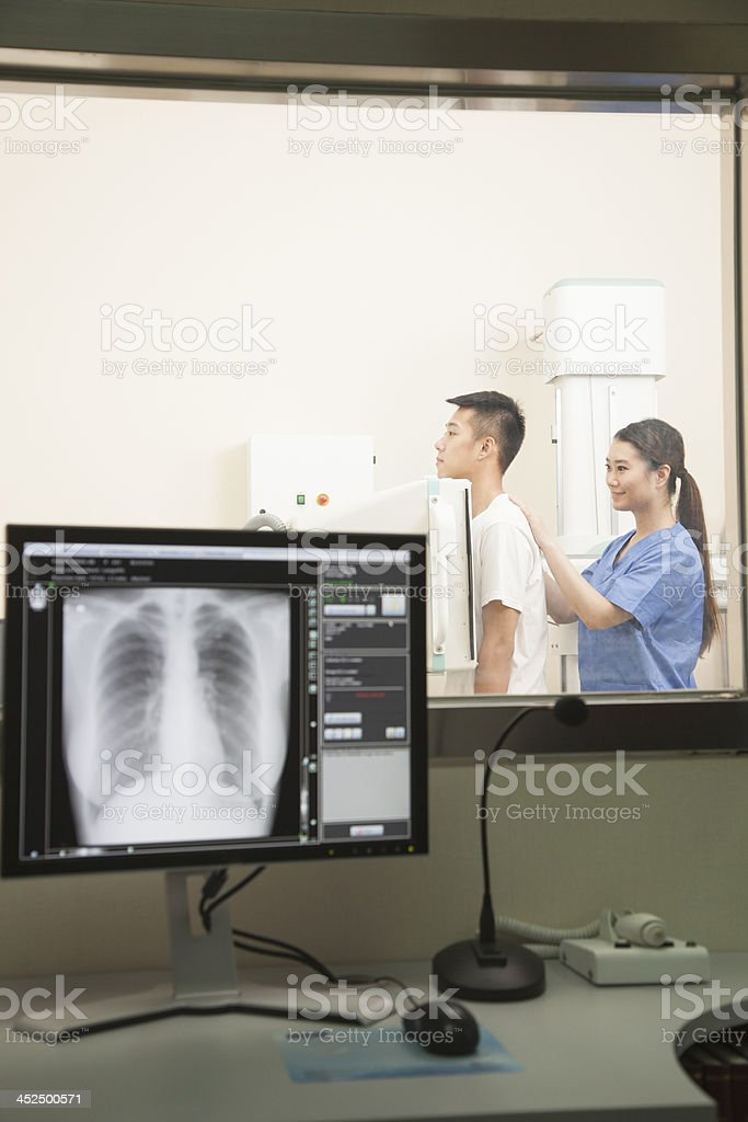 Female Doctor Examining Male Patient's Mid Section With X-ray Machine stock photo