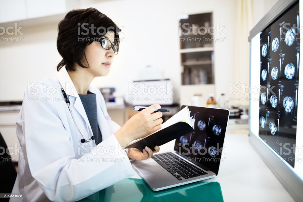 female doctor examining MRIs in hospital stock photo