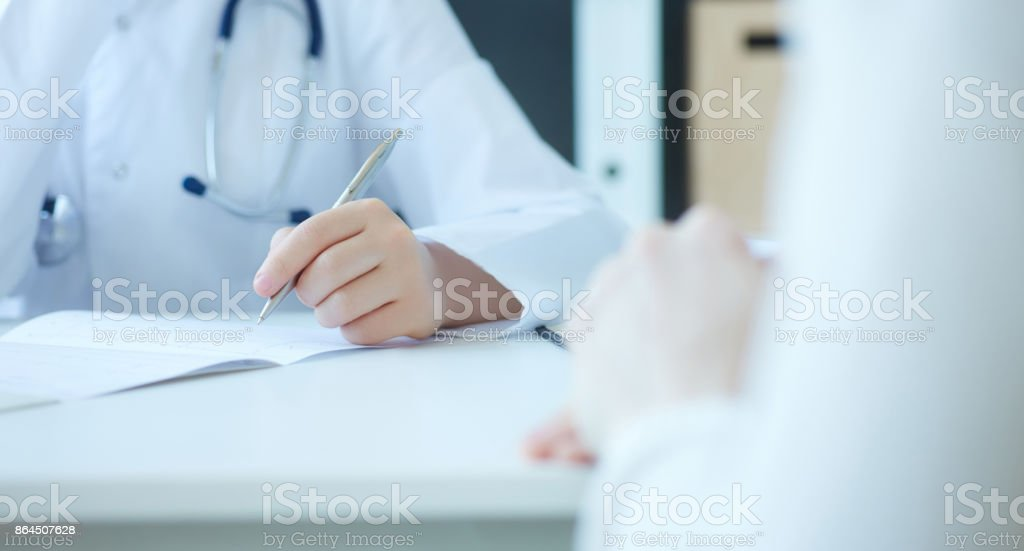 Female doctor examining patient cardiogram chart. Professional conversation, council of cardiologists. Working conference. Medical concept stock photo