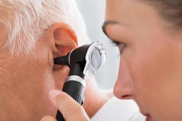 Female Doctor Examining Patient's Ear stock photo
