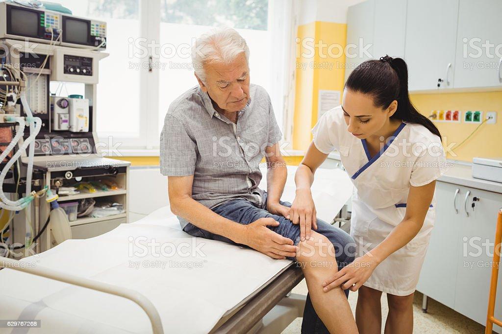 Female doctor examining patients knee stock photo