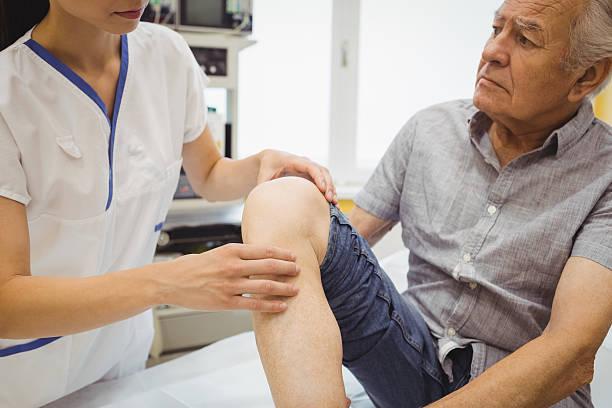 Female doctor examining patients knee ストックフォト