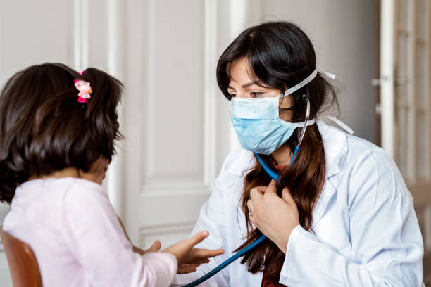 Female doctor examining preschool patient at home stock photo