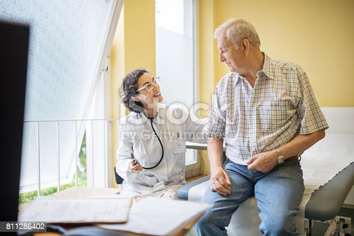 istock Female doctor examining senior male patient at her clinic 811286402