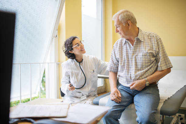 female doctor examining senior male patient at her clinic - doctor visit stock photos and pictures