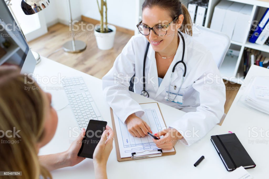Female doctor explaining diagnosis to her patient. stock photo