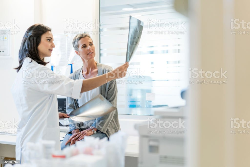 Female doctor explaining x-rays to mature patient stock photo
