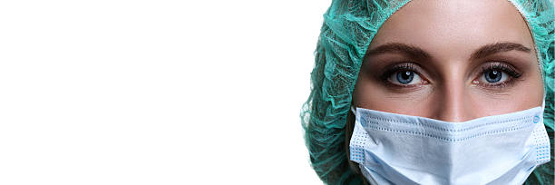 Female doctor face wearing protective mask and green surgeon cap stock photo