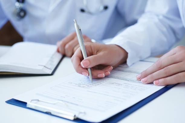 Ärztin, medizinische Formular während der Beratung der Patienten – Foto