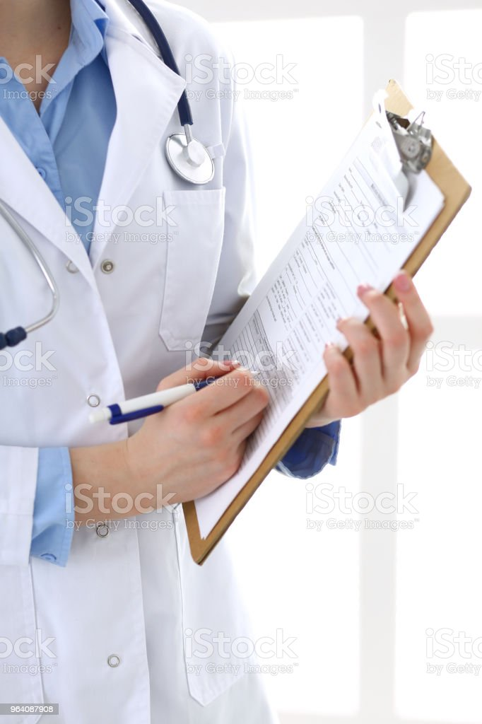 Female doctor filling up medical form on clipboard closeup. Healthcare, insurance and medicine concept - Royalty-free Adult Stock Photo