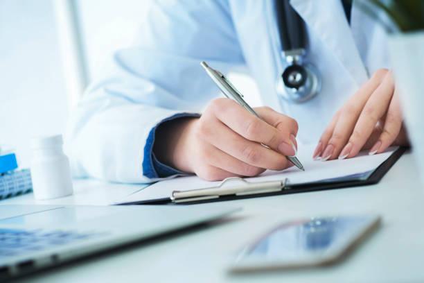 Weiblicher Arzt, der verschreibungspflichtige Formulare ausfüllt oder eine Patientengeschichte während der körperlichen Untersuchung oder Krankheitsvorbeugung am Schreibtisch im Krankenhaus aufnimmt. – Foto
