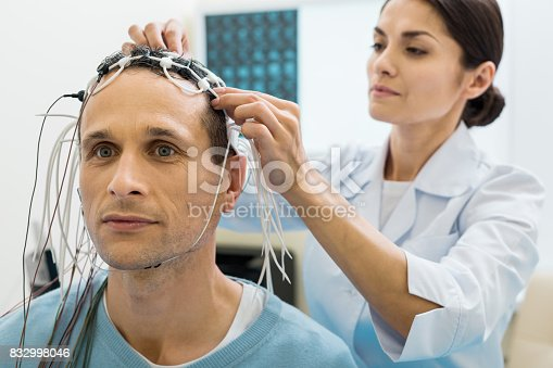 istock Female doctor fixing electrodes on head of patient 832998046
