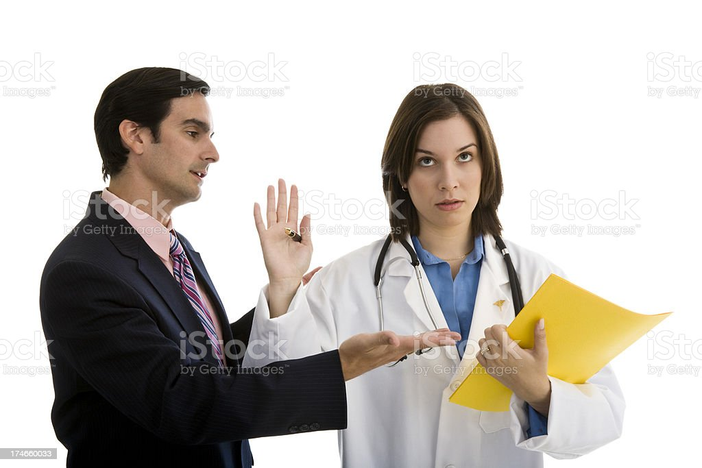 Female doctor gesturing toward businessman to stop stock photo