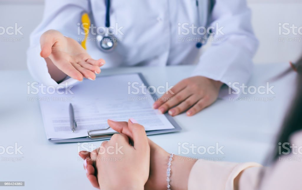 Female doctor giving a consultation to a patient and explaining medical informations and diagnosis. Just hands over the table royalty-free stock photo