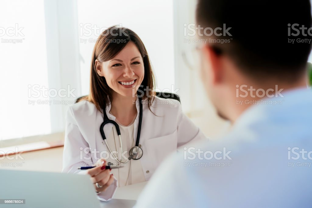 Female doctor giving a consultation to a patient and explaining medical informations and diagnosis. stock photo