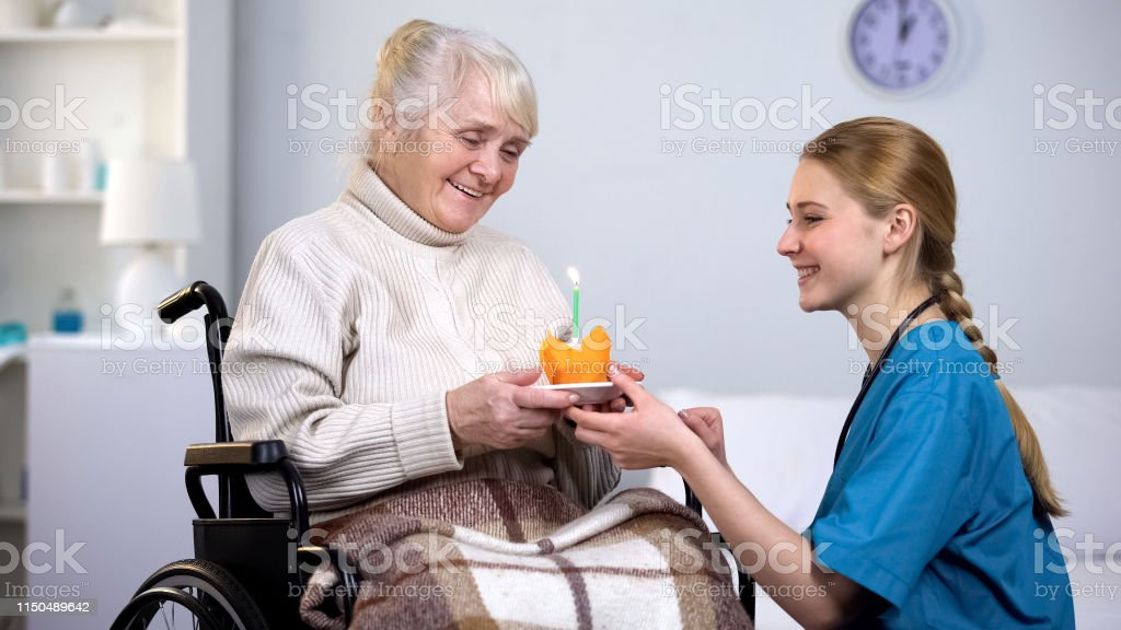 Female doctor giving birthday cake to handicapped woman, nursing home...
