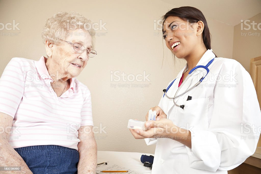 Female Doctor Giving Medication to Senior Patient royalty-free stock photo