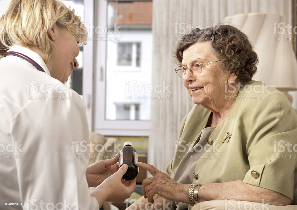 Female doctor going over medication with an elderly female stock photo