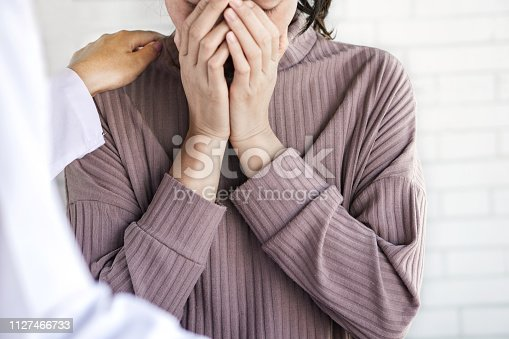 1041630080istockphoto female doctor hand comforting depressed patient at a hospital room 1127466733
