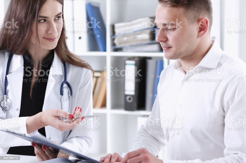 Female doctor hand hold silver pen and showing pad. Physical...
