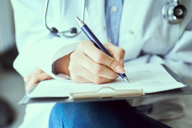Weibliche Arzt Hand halten Silber Stift Füllung PatientenGeschichte Liste an Zwischenablage Pad. Allheilmittel und Lebensrettung, verschreibende Behandlung. – Foto